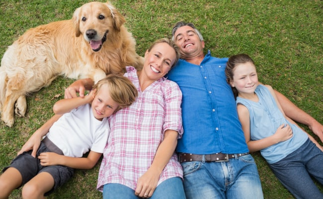 Family-Outside-On-The-Grass-With-Dog