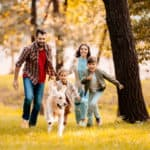 Family-Running-In-The-Park-With-Dog